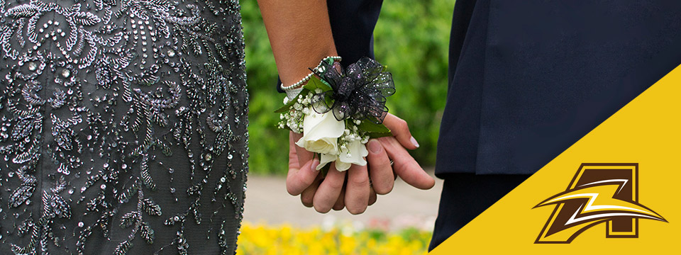 A girl and a boy in prom attire hold hands revealing joined corsages.