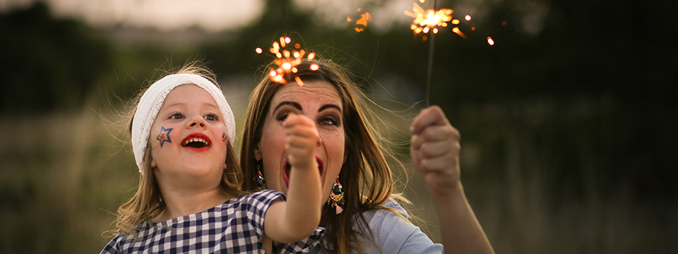 A mother and daughter enjoy 4th of July sparklers together.